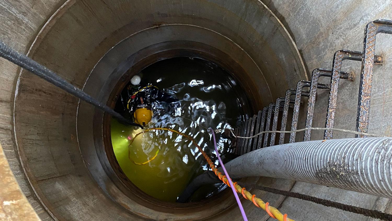 Taucher im Kanal für Drainagereinigung